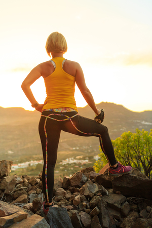 woman sunset: Woman hiking or running in mountains looking at view sunset on mountain top. Female hiker, climber or trail runner with water bottle, looking at beautiful night sunset inspirational landscape.