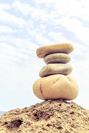 Stones balance and wellness retro spa concept, inspiration, zen-like and well being tranquil composition. Close-up of white pebbles stack over blue sea