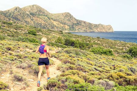 trails: Trail running woman cross country running in mountains on summer beautiful day. Training and working out runner jogging and exercising outdoors in nature, rocky footpath on Crete, Greece