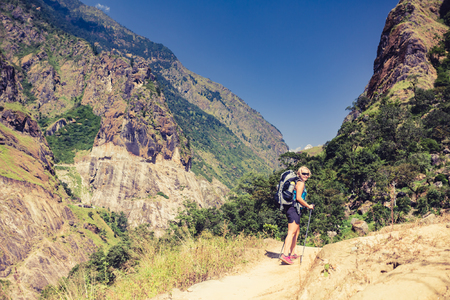 Woman backpacker climbing with backpack in Himalayas, Nepal. Trekking and hiking with backpack in high mountains. Annapurna Himal Range on Annapurna Circuit Trek. Autumn season in Nepal, Asia. Stock Photo