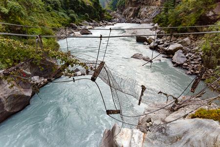 Gebroken Hangbrug in Himalaya Nepal. Kijkend naar rivier in canyon, bos en groene bomen. Annapurna Himal Range op Annapurna Circuit Trek. Herfst seizoen in Nepal, Azië.