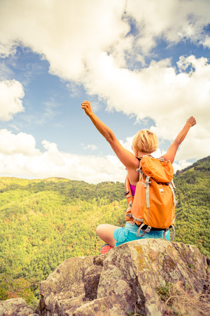Hiking woman celebrating inspirational mountains landscape with arms outstretched. Fitness and healthy lifestyle outdoors in colorful summer nature. Trekking, camping and climbing travel concept.