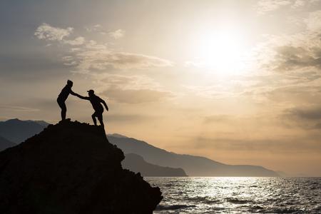 팀웍 손길 돕는 손을 돕는 몇 일출 산에서 실루엣. 등산가 남자와 여자의 팀은 등산 하이킹, 영감을주는 등산, 산 꼭대기에서 서로를 돕습니다.