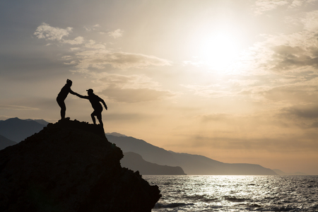 Teamwork couple helping hand trust help silhouette in mountains on sunrise. Team of climbers man and woman help each other on top of mountain, climbing hiking together, inspirational landscape.