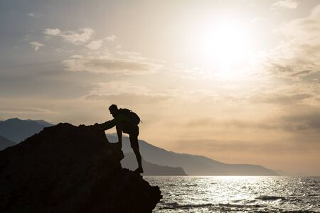 Climbing hiking silhouette in mountains and ocean, rock climber in inspirational sea landscape and islands on mountain peak. Accomplished fit man on sunrise adventure and lifestyle concept.