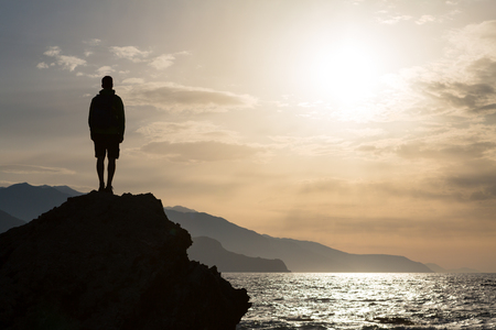 Hiker or runner silhouette backpacker, man looking at inspirational ocean landscape and islands on mountain peak. Accomplished man celebrate beautiful sunrise and sea.Adventure and lifestyle concept. Banco de Imagens
