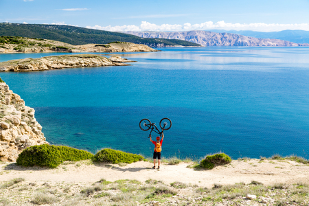 Mountain biker celebrating and looking at inspiring landscape and riding a bike in summer mountains. Man rider cycling MTB on country road or single track. Sport fitness motivation and inspiration.
