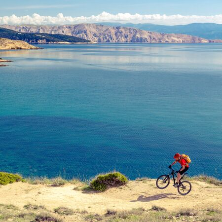 Mountain biker riding on bike in summer or autumn inspirational mountains landscape. Man cycling MTB on enduro trail track at seaside and rocky dirt path. Sport fitness motivation and inspiration. Stock Photo