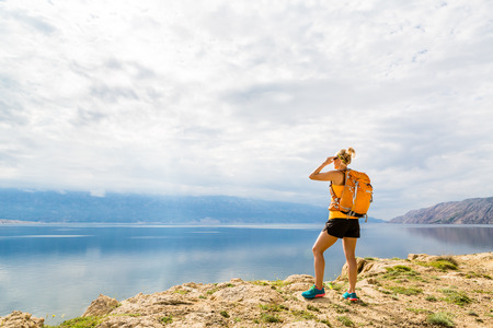 Woman hiker hiking with backpack, looking at sea and mountains view. Recreation and healthy lifestyle outdoors in summer nature. Beautiful inspirational landscape. Trekking and activity concept.