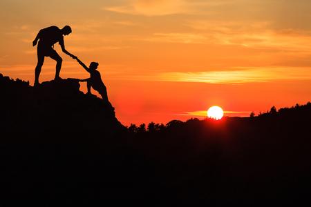 Para pracy zespołowej pomaga sylwetka zaufania strony w inspirujących górach. Zespół wspinaczy pomocy mężczyzna i kobieta turystą, pomagają sobie nawzajem na szczycie góry, piękny zachód słońca krajobraz na Korsyce we Francji