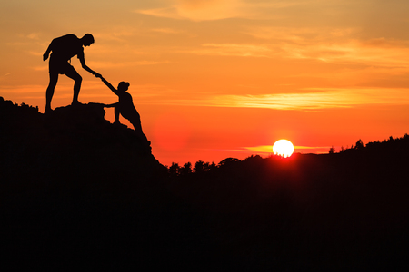 Teamwork couple helping hand trust silhouette in inspiring mountains. Team of climbers assistance man and woman hiker, help each other on top of mountain, beautiful sunset landscape in Corsica France