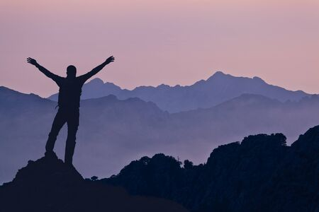 Man successful hiking climbing silhouette in mountains, motivation and inspiration in beautiful sunset. Climber arms up outstretched on mountain top looking at inspiring landscape.