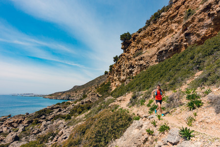 Man running in inspirational mountains at seaside. Young athlete male training and doing workout outdoors in nature. Sport and fitness training inspiration and motivation. Banco de Imagens