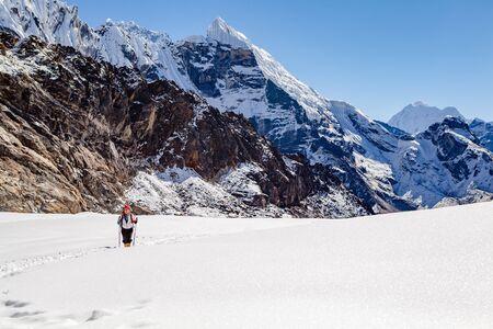 Hiking Woman Crossing Cho La Pass. Himalaya Beautiful Mountain Peaks, Inspirational Autumn Himalayas Landscape in Everest National Park, Nepal. photo