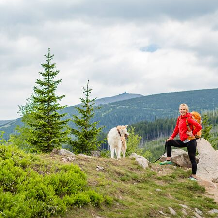 Woman hiking with akita inu dog on mountain trail. Recreation and healthy lifestyle outdoors, summer in mountains and woods, inspirational nature. Fitness, sport, trekking and activity concept. Stock Photo