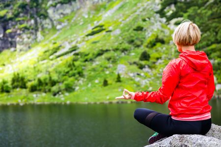Woman meditating in yoga pose in front of mountain lake. Female hiker relaxing in beautiful inspirational mountains landscape. Healthy lifestyle outdoors in nature concept. Stock Photo