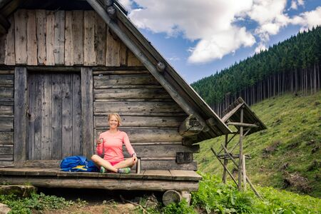 Girl camping and hiking, drinking coffee or tea in beautiful Tatra mountains on hiking trip. Inspirational landscape in Poland. Active woman resting outdoors in summer nature.