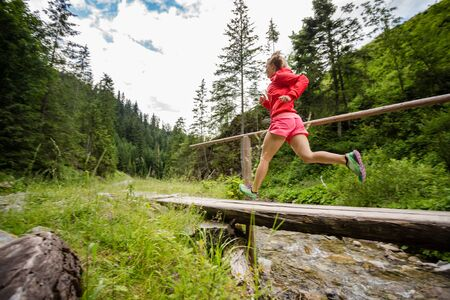Young woman running in mountains on summer sunny day