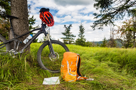 mtb: Mountain biking equipment in the woods, bikepacking adventure trip in green mountains. Travel campsite and MTB cycling with backpack, wilderness forest in Poland. Stock Photo