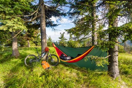 Camping in Holz mit Hängematte und Schlafsack auf Mountainbike Abenteuerreise in grünen Bergen. Reisen Campingplatz bei mtb mit Rucksack Radfahren. Tarp in der Wildnis Wald, Polen. Standard-Bild