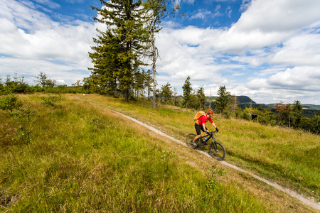 Mountain biking man riding on bike in summer inspirational mountains landscape. Rider cycling MTB on enduro trail path. Sport fitness motivation and inspiration. Rider mountain biker in summer woods. photo