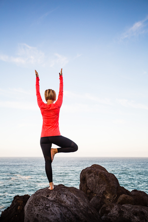 Yoga girl meditating in yoga vrksasana tree pose silhouette at the ocean, beach and rock mountains. Motivation and inspirational fit and exercising. Healthy lifestyle outdoors in nature, fitness concept.