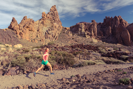 Young woman running in mountains on rocky trail. Cross country runner training in inspiring nature, rocky footpath on Tenerife, Canary Islands Spain. Stock Photo