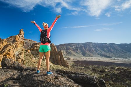 Hiking or climbing success with arms raised concept. Female runner or hiker celebrating on mountain top in inspirational landscape on rocky trail footpath on Tenerife, Canary Islands Spain. Banco de Imagens