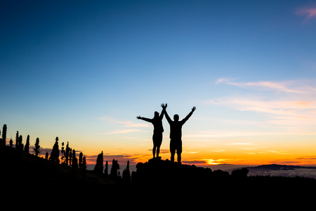 Teamwork couple climbing and reaching mountain peak. Silhouette of climbers team over mountains sunset. Man and woman hikers looking at inspirational landscape on Tenerife Canary Islands, Spain.