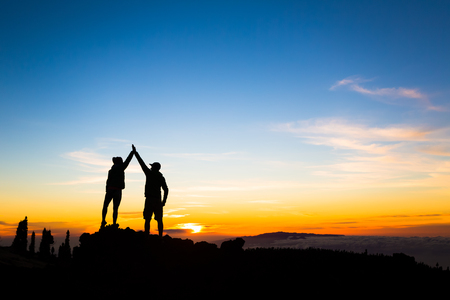 Couple hikers success in sunset mountains, accomplished with arms up outstretched. Man and woman on rocky mountain looking at beautiful sunset inspirational landscape view Tenerife Canary Islands. Banco de Imagens