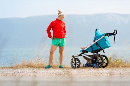 Moeder met kind in wandelwagen die van moederschap genieten bij zonsondergang en bergenlandschap. Jogging of machts lopende vrouw met kinderwagen bij zonsondergang. Mooi inspirerend bergenlandschap.