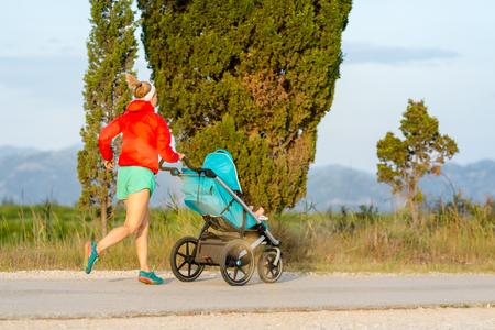 석양과 산 풍경에서 모성을 즐기는 유모차에서 아이 함께 실행 어머니. 조깅이나 전원 일몰에 유모차와 여자 산책. 아름 다운 영감 산 풍경입니다.