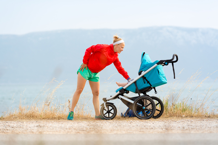 Mother with child in stroller enjoying motherhood at sunset and mountains landscape. Jogging or power walking woman with pram at sunset. Beautiful inspirational mountains landscape. 版權商用圖片