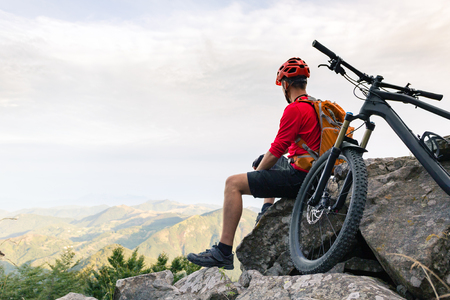 Mountain biker looking at inspiring landscape on bike rocky trail in autumn mountains. Riding on full suspension bike. Sport fitness, motivation and inspiration in beautiful inspirational landscape. Stock Photo
