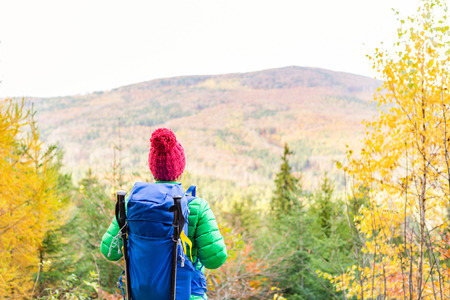 Hiking woman with backpack looking at camera and inspirational autumn golden woods. Fitness travel and healthy lifestyle outdoors in fall season. Travelling female backpacker, walking and looking around.