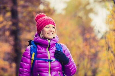 Hiking woman with backpack looking at inspirational autumn golden trees and woods. Fitness travel and healthy lifestyle outdoors in fall season nature. Female backpacker tourist walking in forest. 版權商用圖片