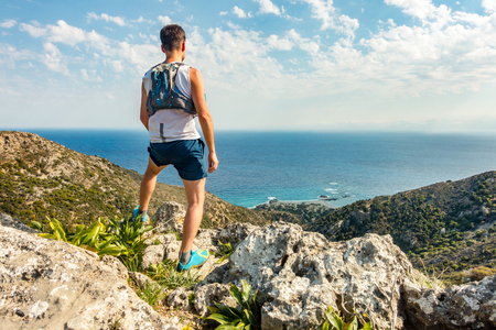 Trail runner looking at inspirational ocean landscape from mountain peak. Accomplished man celebrate beautiful mountains and sea. Adventure and lifestyle concept.