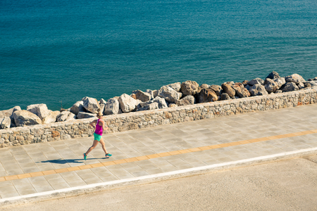 Woman jogging on city street at seaside. Young athlete  training running and doing workout outdoors in urban scene. Sport and fitness training inspiration and motivation. Vintage tone.