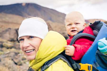 Happy mother with little boy travelling in backpack. Hiking adventure with child on autumn family trip in mountains. Vacations journey with infant carried on back, weekend travel in Tenerife, Spain. Banco de Imagens
