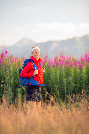 Woman hiking and walking in mountains with backpack. Looking at beautiful view. Travel and trekking in summer nature, inspiring health and fitness concept.