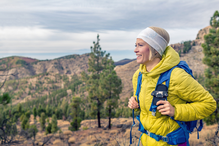 Hiking woman with backpack looking at inspirational mountains landscape and woods. Fitness travel and healthy lifestyle outdoors in fall nature. Female backpacker tourist walking in forest.