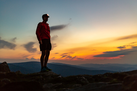 Trail runner with head lamp. Man celebrating sunset on mountain top. Looking at inspiring view. Hiker or climber reached mountain peak, enjoy inspiring landscape on rocky path Karkonosze, Poland Stock Photo