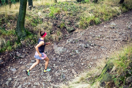 Trail running athletic woman in green forest, sports inspiration and motivation. Female trail runner cross country running. Fitness concept outdoors in nature.