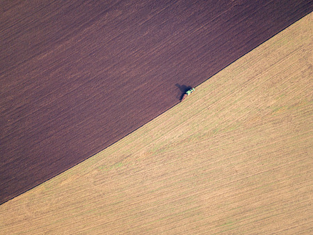 Aerial photo of a tractor ploughing a field in a countryside, blurred motion with focus on tractor. Plowing in autumn season, drone shot.