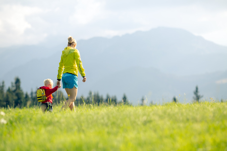 Happy mother with baby boy walking on green meadow. Hiking adventure with child on summer family trip in mountains. Vacations or weekend activity with child.