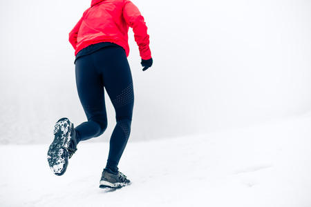 Girl running on snow in winter mountains. Focus on sole of show with snow.