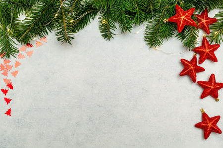 Christmas background with fir tree and red shiny stars on gray concrete table. Top view with copy space. Imagens