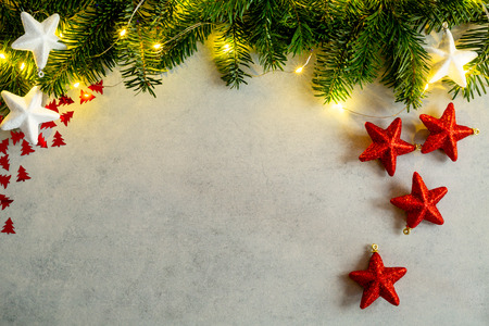 Christmas background with lights, fir tree, white and red shiny stars on gray concrete table. Top view with copy space. Imagens