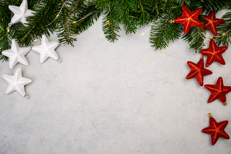 Christmas background with fir tree, white and red shiny stars on gray concrete table. Top view with copy space. Imagens