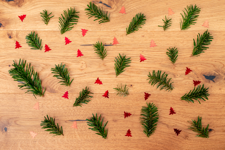 Christmas background with fir tree, red shiny fir trees on brown wooden table. Top flat view with copy space.